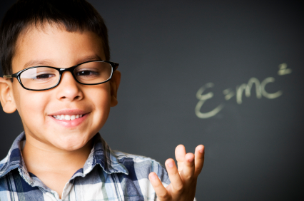 child wearing glasses in front of a chalkboard