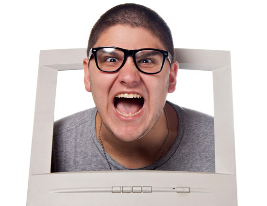 Mad nerdy guy sticking his head through a computer monitor