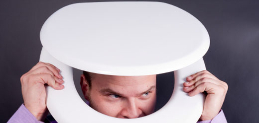 Man peering out from a toilet seat