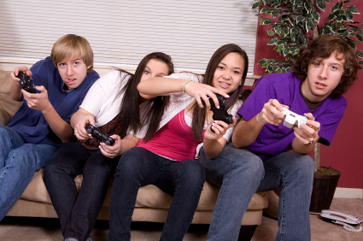 Teenagers sitting on a couch playing video games