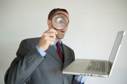 Agent looking at computer with magnifying glass